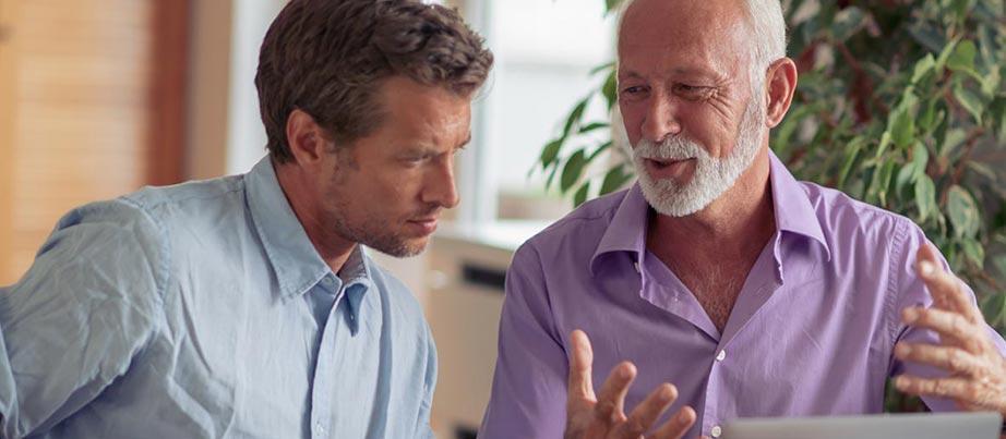 Zwei Männer sind in ein Arbeitsgespräch vertieft.