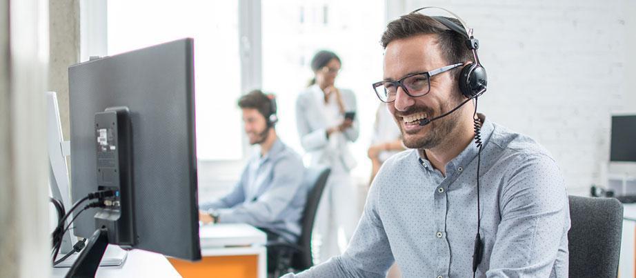 Mann sitzt vor PC mit einem Headset auf
