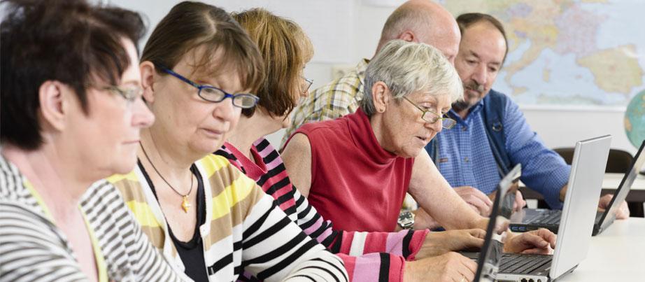 Gruppe älterer Menschen mit Computern