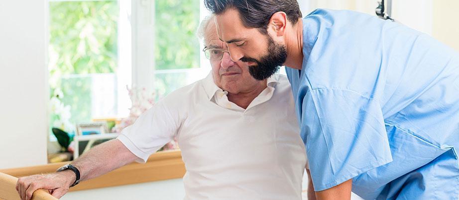 Junger Pfleger hilft einem pflegebedürftigen Senior aus dem Bett