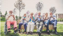 Ältere Menschen mit Smartphone auf einer Bank