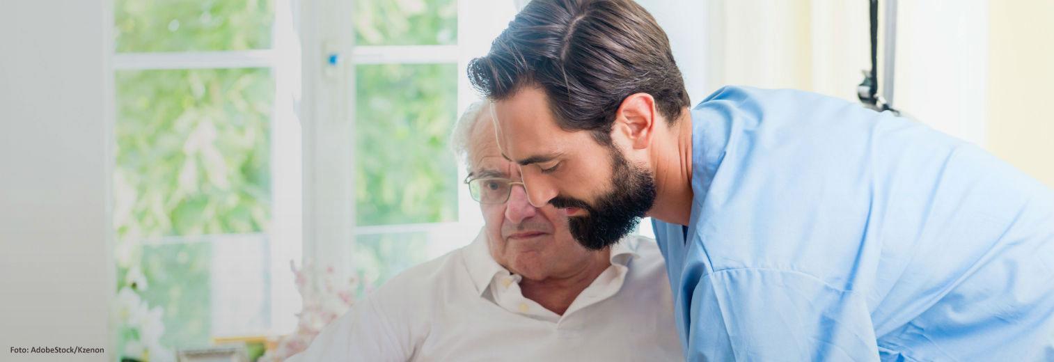 Männliche Pflegekraft hilft Senioren in den Rollstuhl