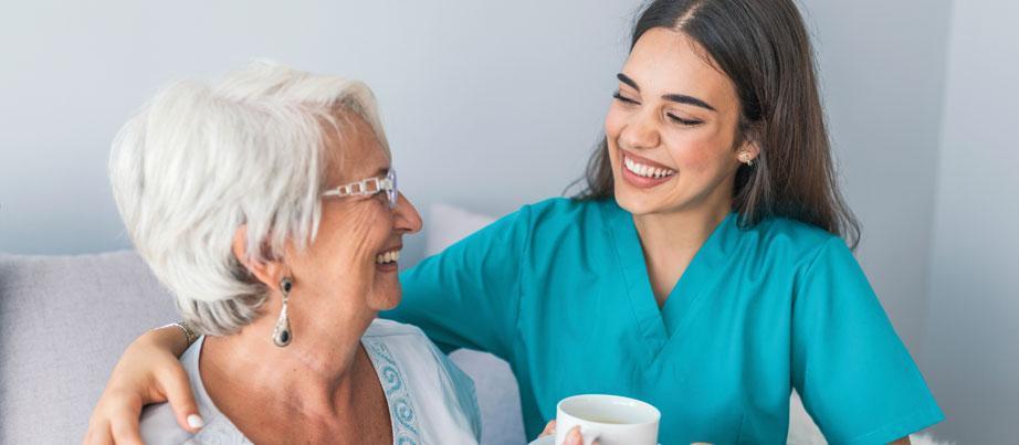 Freundliche Plegerin mit lachender Seniorin