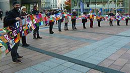 Projektpartnerinnen und -partner vor dem EU-Parlament mit dem 18 m langen Schal der Verbundenheit.