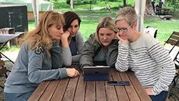 Vier Frauen sehen sich etwas auf einem Tablet an