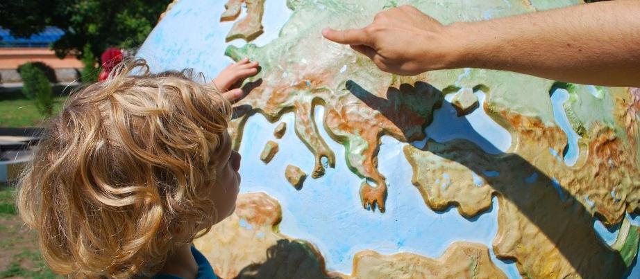 Kind zeigt auf Globus
