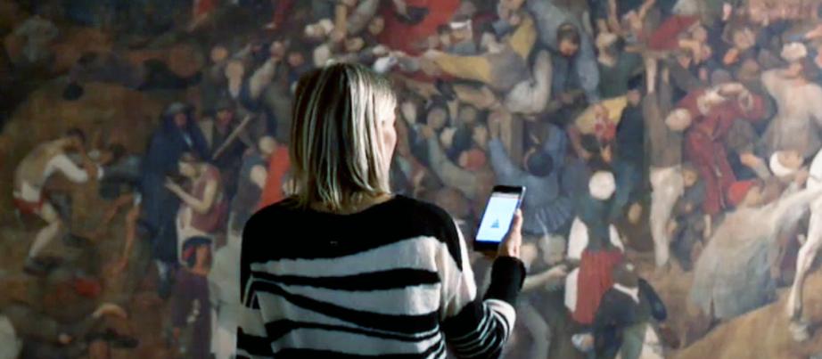 Frau mit Handy vor einem Wandgemälde