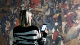 Frau mit Handy vor einem Gemälde