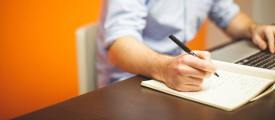 Person sitzt am Schreibtisch mit Stift und Block