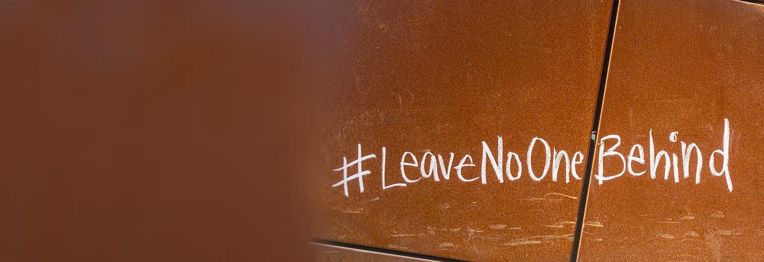 Mit Kreide auf roten Boden geschriebener, englischssprachiger Hashtag Leave No One Behind