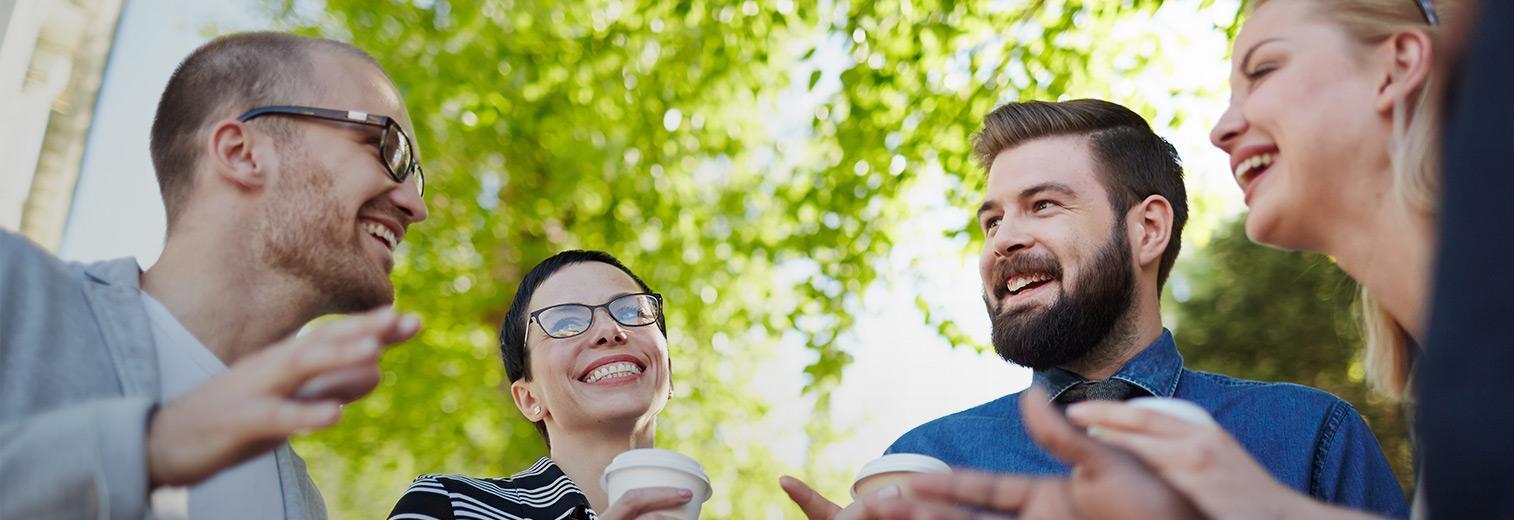 Vier freundliche Personen sind im Gespräch, im Hintergrund sind Bäume zu erkennen