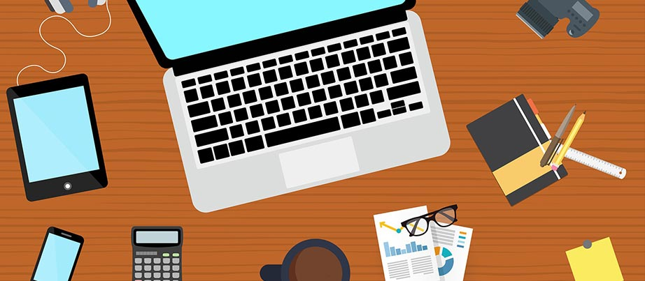 Schreibtisch mit verschiedenen Arbeitsmaterialien wie unter anderem Laptop und Zeichenblock.