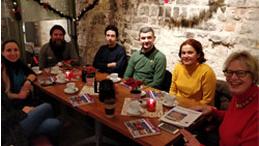 Die Projektgruppe sitzt um einen Tisch herum.