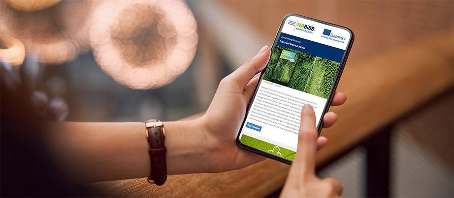 eine Hand hält ein Mobiltelefon, auf dem der Newsletter zu sehen ist
